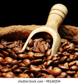 Coffee beans on burlap sack with wooden scoop