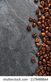Coffee beans on dark stone table. Flat lay with copy space.
