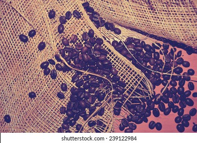 Coffee beans on grunge wooden background with sackcloth