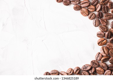 Coffee beans on a light white gray concrete table background with place for text.