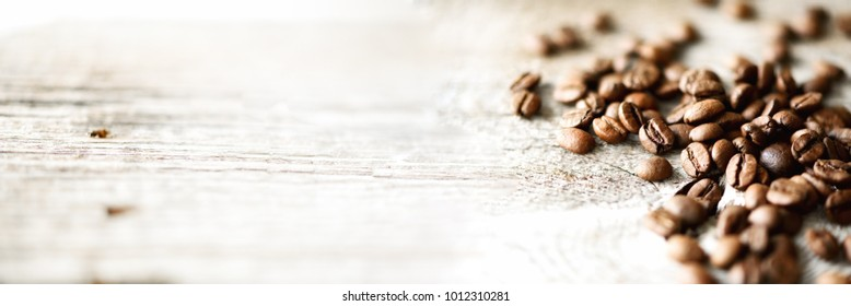 Coffee beans on light wooden background with copyspace for text. Coffee background, food frame, texture concept. Banner