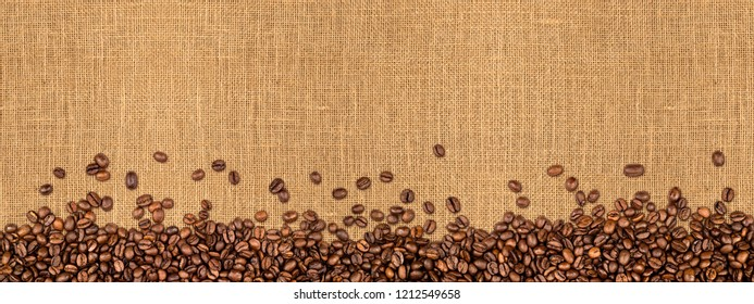 coffee beans on natural burlap texture wide panorama background