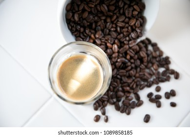 Coffee Beans on white countertop with espresso shot