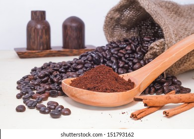 Coffee beans on wood spoon and raw coffee beans