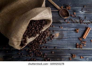 Coffee beans on the wooden background, jute bag and spices