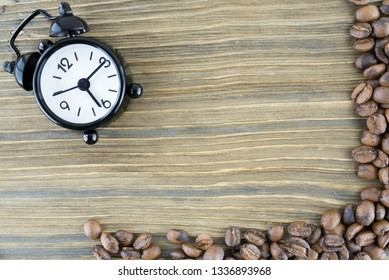 Сlock and coffee beans on wooden background. Natural photo.