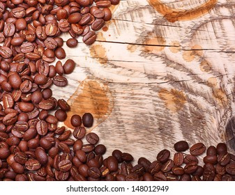 Coffee beans on wooden background with coffee stains.