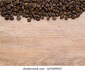 Coffee beans on wooden background. Pile of coffee.