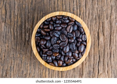 coffee beans on wooden bowl isolated top viwe on old wood background.