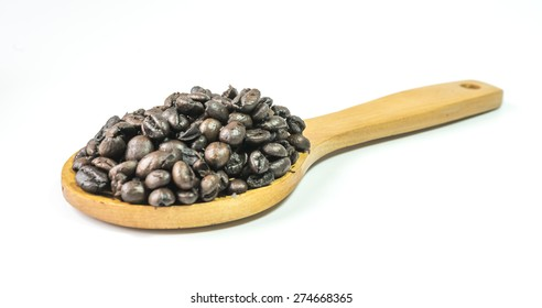 Coffee beans on a wooden ladle