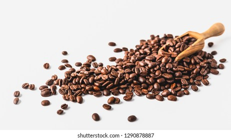 Coffee beans on a wooden scoop and a white background