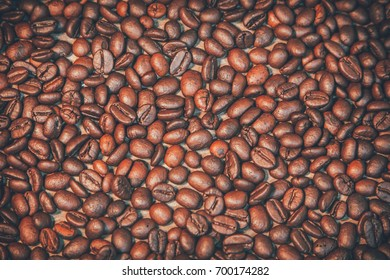 Coffee beans placed on old wooden boards with free space for backgrounds. Presented in vintage color scheme.