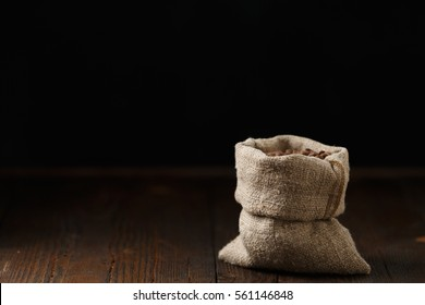 Coffee beans in a pouch on a wooden desk