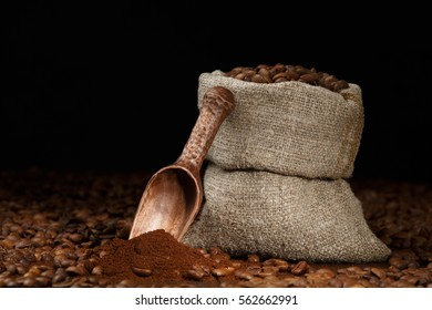 Coffee beans in a pouch with a scoop on a wooden desk