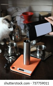 Coffee beans are poured into a coffee grinder. Empty label