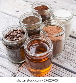 Coffee beans, coffee powder, creamer, cocoa powder, honey and processed tea leaves in a mason jar over weathered wooden background