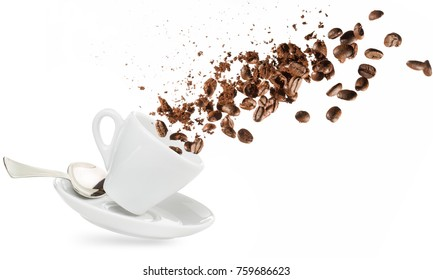 coffee beans and powder spilling out of a cup isolated on white