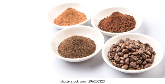 Coffee beans, powdered coffee, chocolate powder and processed tea leaves beverages in white bowl over white background