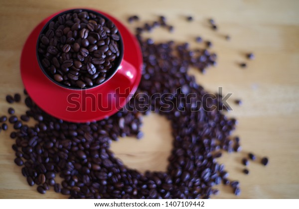 coffee beans in red cup and beans with heart shape in background