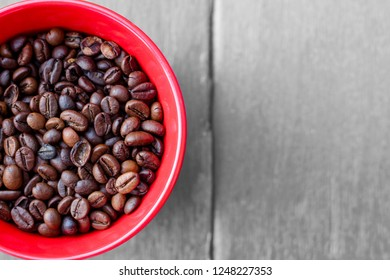 Coffee beans in the red mug over the wooden table. Colour Splash effect