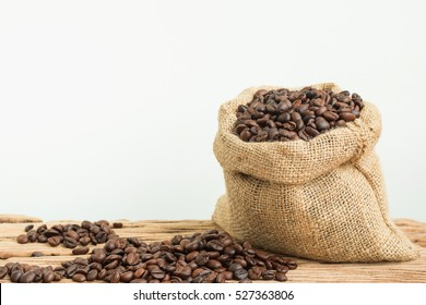 Coffee beans in a sack on wooden table.