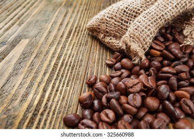 Coffee beans in sackcloth bag on wooden table. Close up. Selective focus