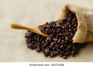 Coffee beans in sackcloth bag on brown paper background.