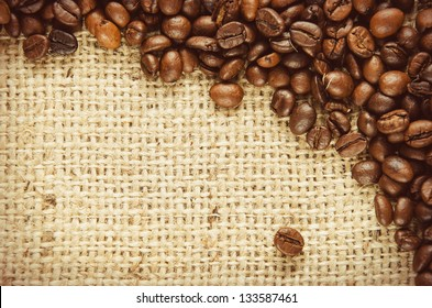Coffee beans scattered on burlap can be used as background. Toned picture