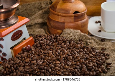 coffee beans are scattered on burlap against the background of a manual coffee grinder, sugar bowl and a cup with a saucer