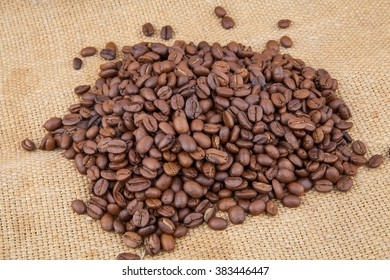 Coffee beans scattered on burlap, food photo
