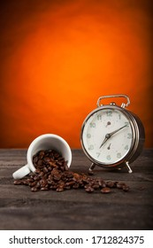Coffee beans scattered on a surface near a small cup and an alarm clock on a table, isolated on orange background