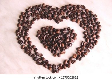 coffee beans in the shape of a heart in the heart, after roasting on the table, selective focus. lots of heart-shaped coffee beans in the heart, background.