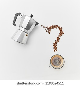 Coffee beans in the shape of question marks, a cup of strong coffee and a metal coffee maker on a gray background with space for text. Flat lay