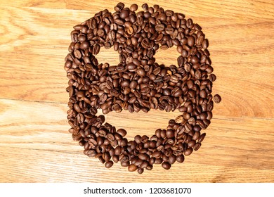 Coffee Beans Shaped into Face on Brown Wooden Bench. Top View
