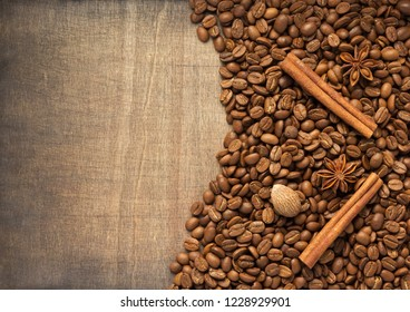 coffee beans and spices on wooden background, top view