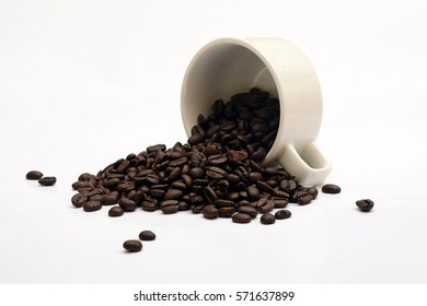 Coffee Beans spill from white cup