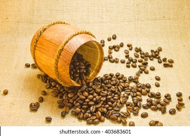 Coffee beans spilled from a lying wooden jar on the background of a sacking
