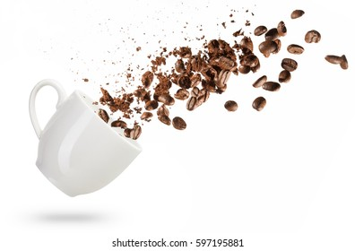 coffee beans spilled out of a cup isolated on white background