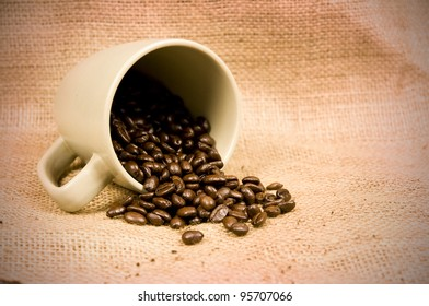 coffee beans spilling from mug on hessian with copy space