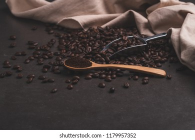 Coffee beans with spoon on brown background