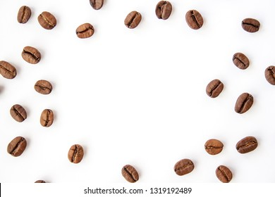 Coffee beans spread over white background. Empty in the middle.