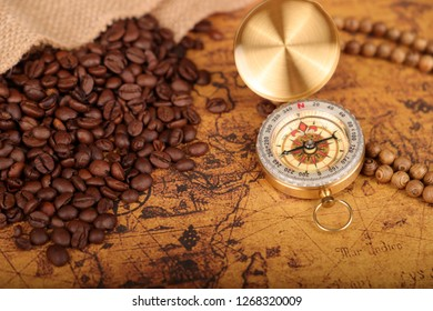 Coffee Beans and Vintage compass on an old world map - trade and explorer concept