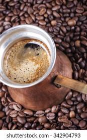 Coffee beans, vintage copper coffee pot closeup, cezve or ibrik