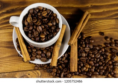 Coffee beans in white cup and cinnamon sticks on wooden table. Top view