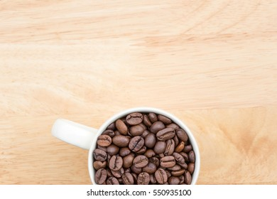 Coffee beans in white cup with copy space.