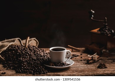Coffee beans white cup of fragrant coffee and coffee grinder on wooden table on black background