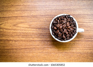 Coffee beans in white cup on wooden table.