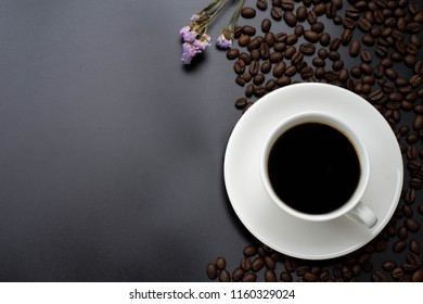 Coffee with coffee beans in a white cup and on a black background.