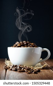 Coffee beans in a white cup on a wooden surface and dark background