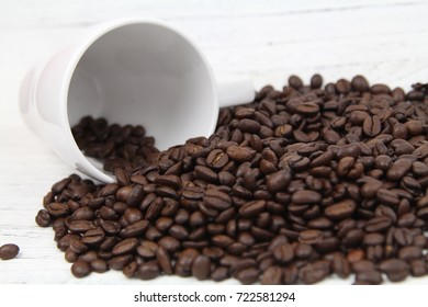 Coffee Beans with White Cup over wooden background. Copy Space Concept
